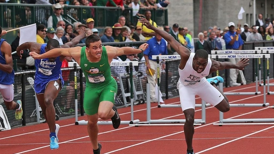 FILE - In this June 14, 2014, file photo, Oregon's Devon Allen, front left, and Texas A&M's Wayne Davis II reach for the finish line during the men's 110-meter hurdles at the NCAA track and field championships on, in Eugene, Ore. In June, Allen won the NCAA championship in the 110-meter hurdles. Two months later, he's won the job a starting receiver for the No. 3 Ducks. Allen, a redshirt freshman, will start along with senior Keanon Lowe at receiver when Oregon hosts South Dakota in the opener on Saturday night. (AP Photo/Rick Bowmer, File)