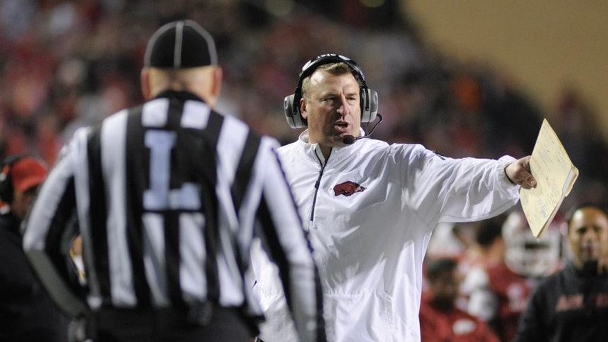 FILE - In this Nov. 2, 2013, file photo, Arkansas coach Bret Bielema talks to an official in the second half of an NCAA college football game in Fayetteville, Ark. The NCAA's switch to a 40-second play clock in 2008 altered the way college football games were managed, the pace of play no longer in the hands of the officials but the two teams' offenses. With defenses struggling to keep up, the NCAA football rules committee earlier this year looked at possibly prohibiting teams from snapping the ball until at least 10 seconds had run off the 40-second play clock. Supporters of the rule, like Arkansas' Bret Bielema and Alabama's Nick Saban, argued it was needed to allow teams to substitute for fatigued players and prevent injuries. (AP Photo/Beth Hall, File)