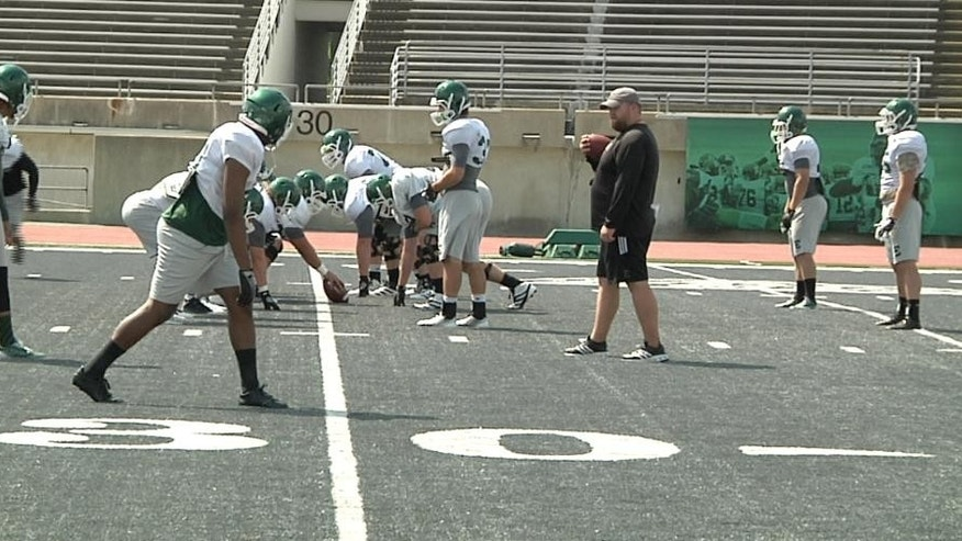 In this photo taken on Aug. 15, 2014, Eastern Michigan players line up for a play during NCAA college football practice at Rynearson Stadium in Ypsilanti, Mich.. The school has replaced the stadium's green artificial turf with gray FieldTurf. (AP Photo/Mike Householder)