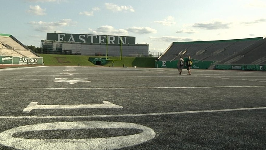 In this photo taken on Aug. 15, 2014, a pair Eastern Michigan players walks across he field after NCAA college football practice at Rynearson Stadium in Ypsilanti, Mich.. The school has replaced the stadium's green artificial turf with gray FieldTurf. (AP Photo/Mike Householder)