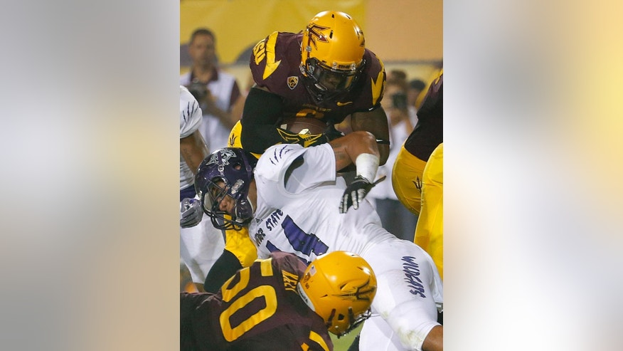 Arizona State running back Kalen Ballage, top, scores a touchdown as Weber State linebacker Emmett Tela, middle, defends during the first half of an NCAA college football game, Thursday, Aug. 28, 2014, in Tempe, Ariz. (AP Photo/Matt York)