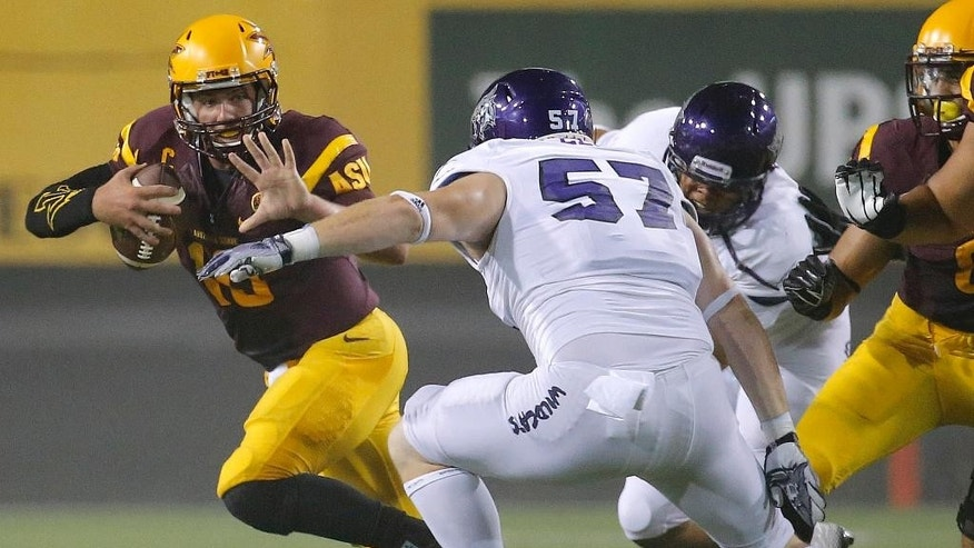 Arizona State quarterback Taylor Kelly tries to avoid a sack by Weber State tackle Jake Gallegos (57) during the first half of an NCAA college football game, Thursday, Aug. 28, 2014, in Tempe, Ariz. (AP Photo/Matt York)