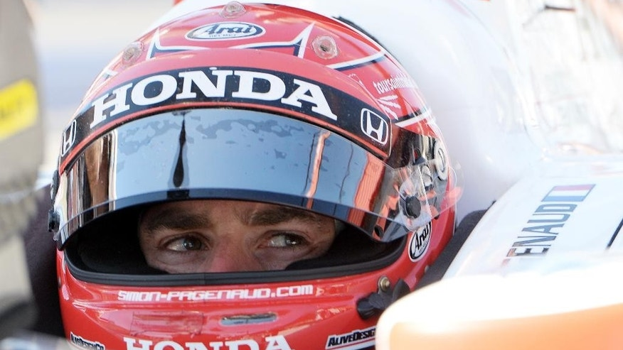 Simon Pagenaud sits in his race car as he waits for practice for Saturday's Indycar auto race Friday, Aug. 29, 2014, at Auto Club Speedway, in Fontana, Calif. (AP Photo/Will Lester)