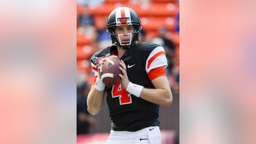 FILE - In a Dec. 24, 2013, file photo Oregon State quarterback Sean Mannion looks for an open receiver in the second quarter of the Hawaii Bowl NCAA college football game against Boise State, in Honolulu. The once the soft-spoken and reserved quarterback for the Oregon State has blossomed into a confident full-fledged leader in his senior season for the Beavers.  (AP Photo/Eugene Tanner, file)