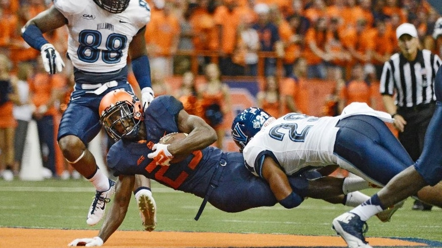 Syracuse's Devante McFarlane, center, gets tackled by Villanova's Jerry Miles during an NCAA college football game at the Carrier Dome, Friday, Aug. 29, 2014 in Syracuse, N.Y. (AP Photo/Heather Ainsworth)