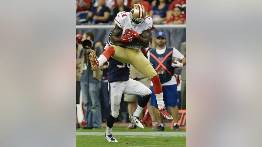 San Francisco 49ers' Kassim Osgood (14) makes a catch as he is hit by Houston Texans' Andre Hal (38) during the second quarter of an NFL football preseason game Thursday, Aug. 28, 2014, in Houston. (AP Photo/David J. Phillip)