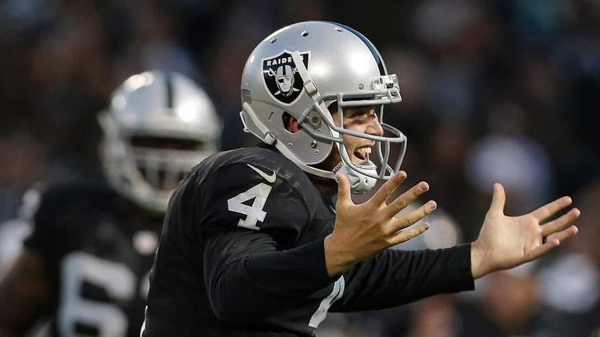 Oakland Raiders quarterback Derek Carr, right, celebrates after throwing a 20-yard touchdown pass to Mychal Rivera against the Seattle Seahawks during the first half of an NFL preseason football game in Oakland, Calif., Thursday, Aug. 28, 2014. (AP Photo/Marcio Jose Sanchez)