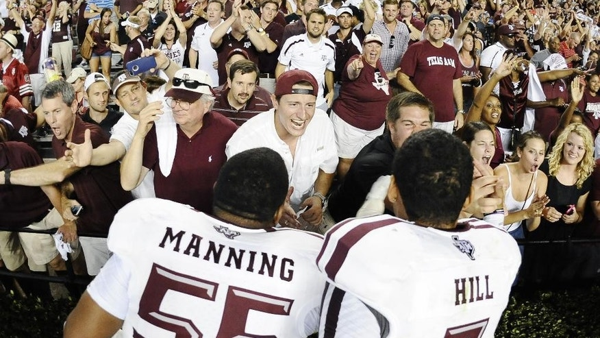 Texas A&M defensive lineman Justin Manning (55) and quarterback Kenny Hill (7) celebrate with fans after defeating South Carolina 52-28 in an NCAA college football game on Thursday, Aug. 28, 2014, in Columbia, S.C. (AP Photo/Rainier Ehrhardt)