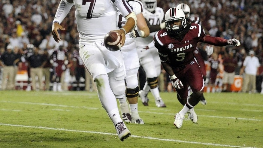 Texas A&M quarterback Kenny Hill (7) runs as South Carolina linebacker Sharrod Golightly (9) defends during the second half of an NCAA college football game on Thursday, Aug. 28, 2014, in Columbia, S.C. (AP Photo/Rainier Ehrhardt)