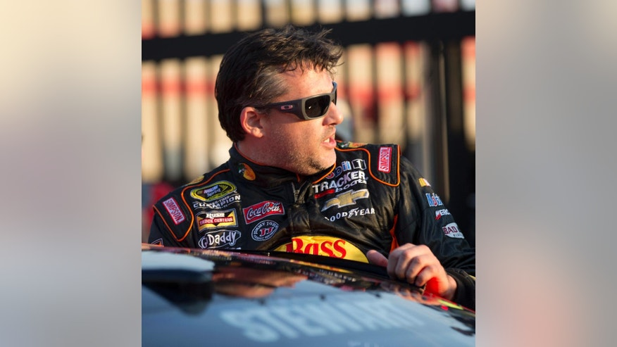 Sprint Cup Series driver Tony Stewart (14) climbs into his car as he prepares to qualify for Sunday's Oral B USA 500 NASCAR auto race at Atlanta Motor Speedway Friday, Aug. 29, 2014, in Hampton, Ga. (AP Photo/John Bazemore)