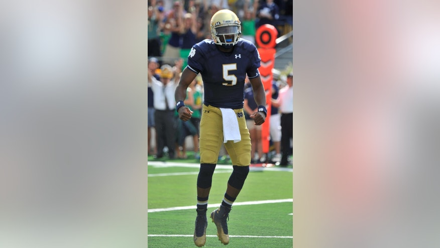CORRECTS TO EVERETT NOT EVERTT - Notre Dame quarterback Everett Golson reacts after scoring a touchdown during an NCAA college football game with Rice in South Bend, Ind., Saturday, Aug. 30, 2014. (AP Photo/Joe Raymond)