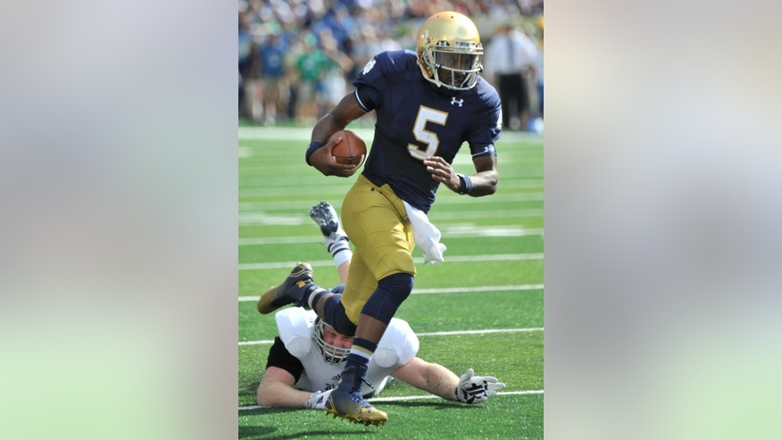 CORRECTS TO EVERETT NOT EVERTT - Notre Dame quarterback Everett Golson (5) heads toward the end zone during an NCAA college football game with Rice in South Bend, Ind., Saturday, Aug. 30, 2014. (AP Photo/Joe Raymond)