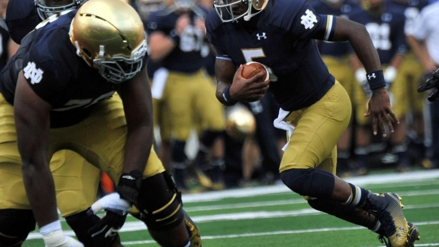 Notre Dame quarterback Everett Golson heads toward the end zone for a touchdown during an NCAA college football game against Rice in South Bend, Ind., Saturday Aug. 30, 2014. (AP Photo/Joe Raymond)