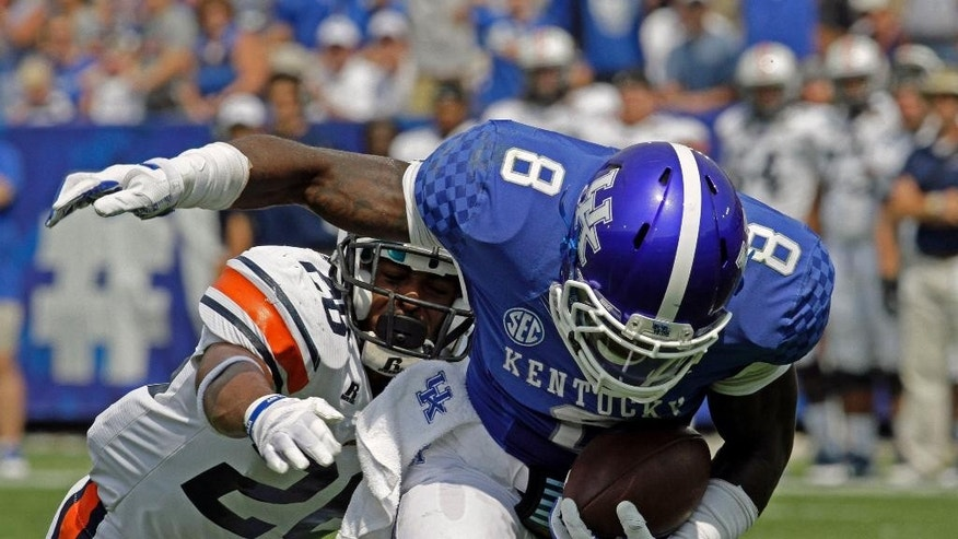 Kentucky wide receiver Javess Blue (8) maintains his balance after grabbing a pass in front of Tennessee-Martin safety Walter Evans (26) in the first half of an NCAA college football game in Lexington, Ky., Saturday, Aug. 30, 2014. (AP Photo/Garry Jones)