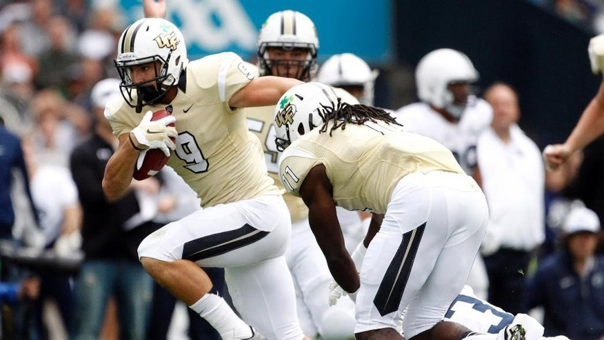 UCF Knights J.J. Worton, left, playing against Penn State Nittany Lions during the Croke Park Classic College Football match in Dublin, Ireland, Saturday, Aug. 30,2014. University of Central Florida hosted Penn State in their 2014 football Season Opener Saturday. This big season opener for UCF and Penn State is the first time that they have played outside the United States.  (AP Photo/Peter Morrison)