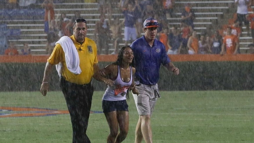 A football fan is escorted off the playing field by security before she was arrested by local police during a weather delay in an NCAA college football game between Florida and Idaho in Gainesville, Fla., Saturday, Aug. 30, 2014. (AP Photo/John Raoux)
