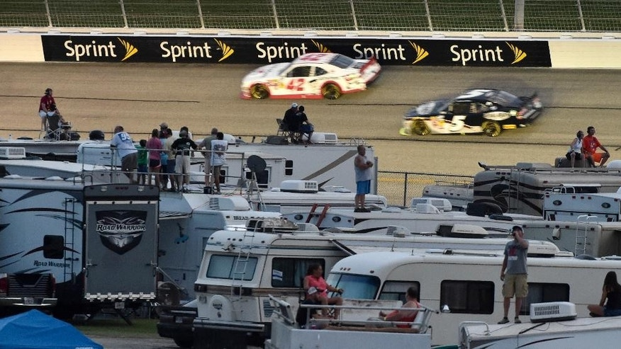NASCAR fans in the infield watch Nationwide Series drivers Kyle Larson (42) and Kasey Kahne (5) during the NASCAR Nationwide Cup Series Great Clips 300 auto race at Atlanta Motor Speedway, Saturday, Aug. 30, 2014 in Hampton, Ga. (AP Photo/David Tulis)