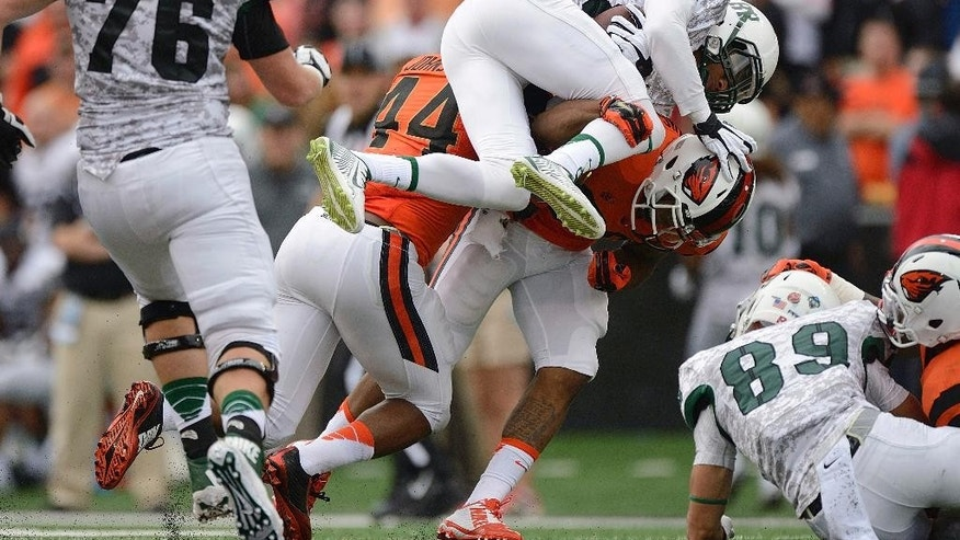 Portland State receiver Darnell Adams (82) is tackled by Oregon State safety Justin Strong during an NCAA college football game in Corvallis, Ore., Saturday, Aug. 30, 2014. (AP Photo/Troy Wayrynen)