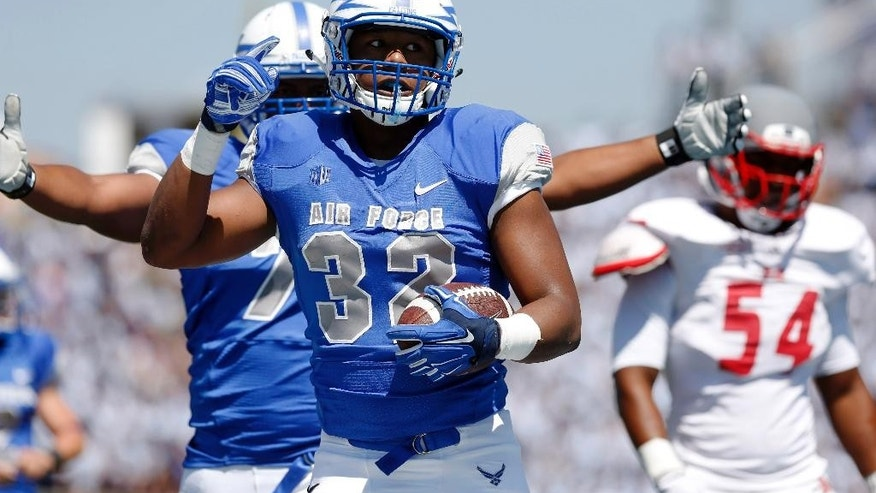 Air Force running back Broam Hart, front, celebrates his touchdown run as Nicholls State linebacker Ronnie Walker, back, looks on in the second quarter of an NCAA college football game at Air Force Academy, Colo., on Saturday, Aug. 30, 2014. (AP Photo/David Zalubowski)