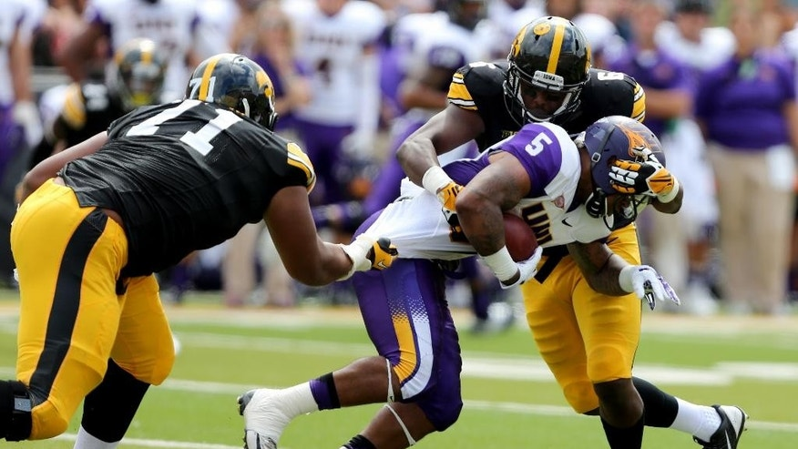 Iowa defensive lineman Carl Davis (71) and linebacker Reggie Spearman tackle Northern Iowa running back Darrian Miller during the first half of an NCAA college football game, Saturday, Aug. 30, 2014, in Iowa City, Iowa. (AP Photo/Justin Hayworth)