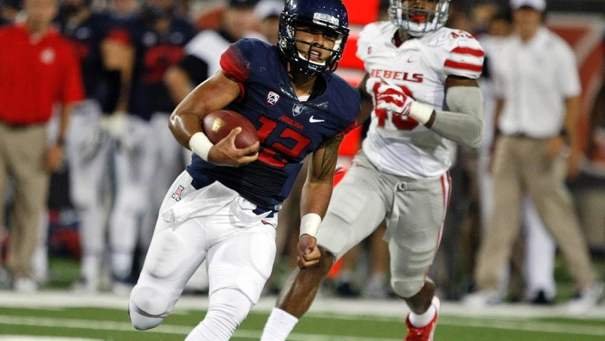 Arizona quarterback Anu Solomon (12) runs for a first down against UNLV during the first half of an NCAA college football game, Friday, Aug. 29, 2014, in Tucson, Ariz. (AP Photo/Rick Scuteri)