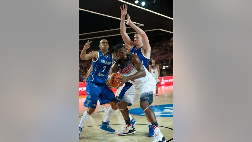 United States's Kenneth Faried, center,  duels for the ball beside Finland's Erik Murphy, right, and Shawn Huff,during the Group C Basketball World Cup match between United States and Finland,  in Bilbao northern Spain, Saturday, Aug. 30, 2014. The 2014 Basketball World Cup competition will take place in various cities in Spain from Aug. 30 through to Sept. 14. (AP Photo/Alvaro Barrientos)