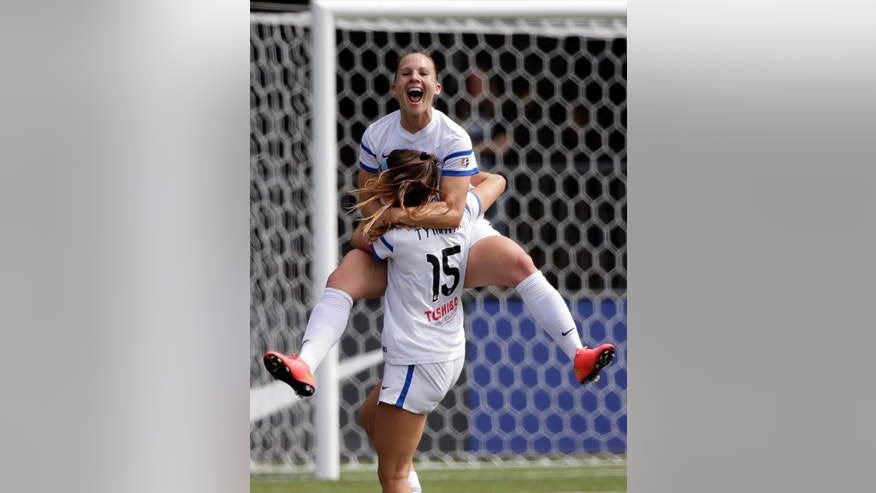 FC Kansas City's Amy Rodriguez leaps into the arms of teammate Erika Tymrak (15) after scoring against the Seattle Reign FC in the first half of the NWSL championship soccer match Sunday, Aug. 31, 2014, in Tukwila, Wash. (AP Photo/Elaine Thompson)