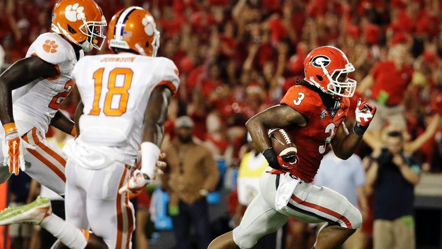 Georgia's Todd Gurley, right, runs the ball to score a touchdown in the second half of an NCAA college football game against Clemson, Saturday, Aug. 30, 2014, in Athens, Ga. Gurley ran for 198 yards and three touchdowns, returned a kickoff 100 yards for another score, and No. 12 Georgia gained some early style points in the national race with a 45-21 victory over No. 16 Clemson on Saturday night. (AP Photo/David Goldman)