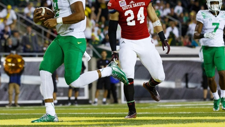 Oregon quarterback Marcus Mariota (8) runs into the end zone for a touchdown during the second quarter of an NCAA college football game against South Dakota in Eugene, Ore., Saturday, Aug. 30, 2014. (AP Photo/Ryan Kang)