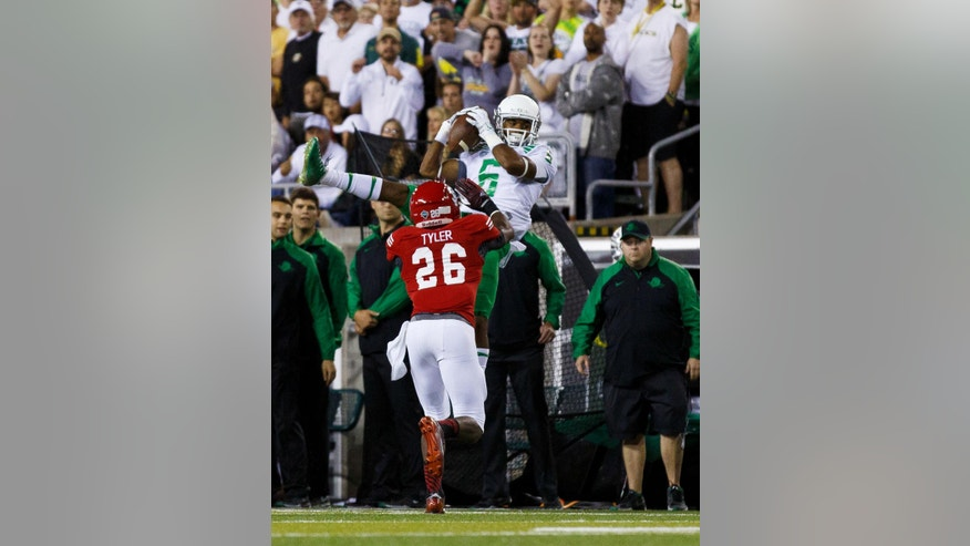 Oregon wide receiver Charles Nelson (6) makes a catch as South Dakota's Chris Tyler defends during the second quarter of an NCAA college football game in Eugene, Ore., Saturday, Aug. 30, 2014. (AP Photo/Ryan Kang)