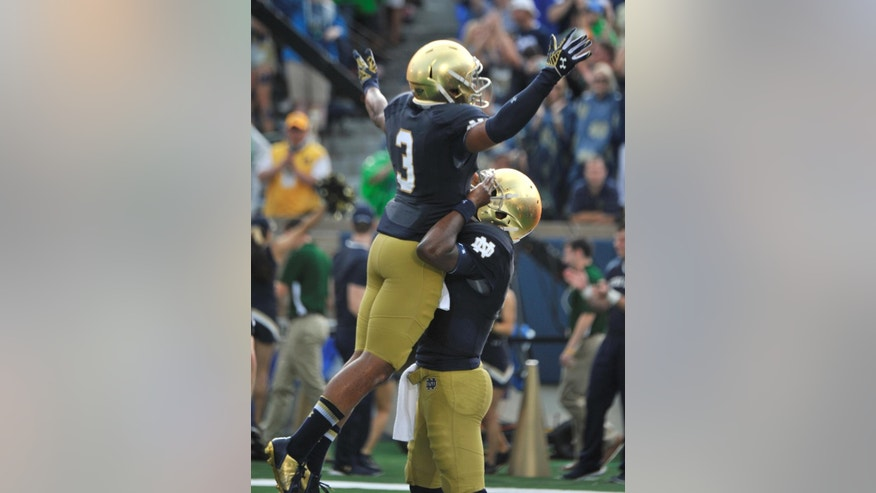 Notre Dame quarterback Everett Golson, right, holds up wide receiver Amir Carlisle in the end zone after Golson's third running touchdown during an NCAA college football game with Rice in South Bend, Ind., Saturday, Aug. 30, 2014. Notre Dame won 48-17. (AP Photo/Joe Raymond)