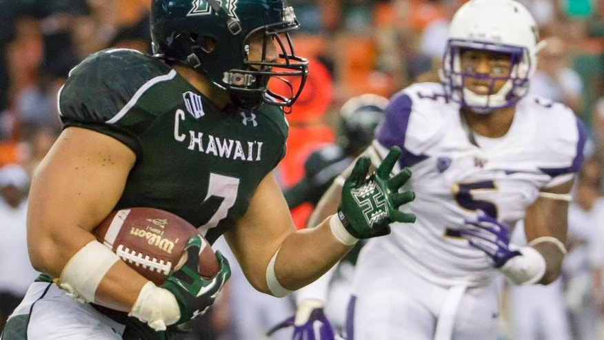 Hawaii running back Joey Iosefa (7) looks for an opening as Washington defensive lineman Joe Mathis (5) watches the third quarter of an NCAA college football game, Saturday, Aug. 30, 2014, in Honolulu. (AP Photo/Eugene Tanner)