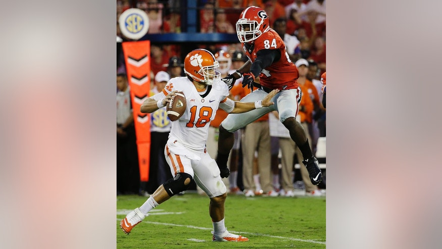 Clemson quarterback Cole Stoudt, left, scrambles to get away from the defense of Georgia's Leonard Floyd in the second half of an NCAA college football game, Saturday, Aug. 30, 2014, in Athens, Ga. Georgia won 45-21. (AP Photo/David Goldman)