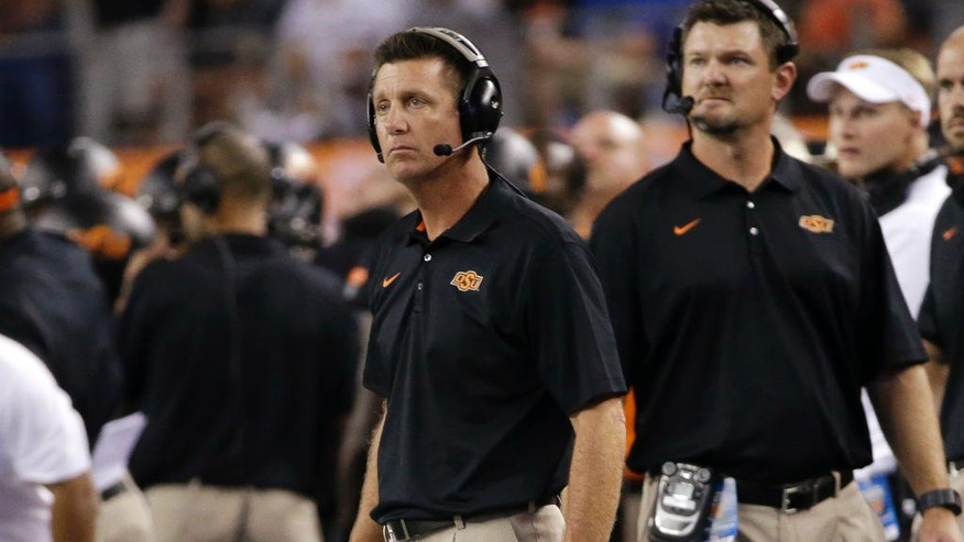 Oklahoma State coach MIke Gundy, center, watches play in the first half of an NCAA college football game against Florida State, Saturday, Aug. 30, 2014, in Arlington, Texas. (AP Photo/Tony Gutierrez)