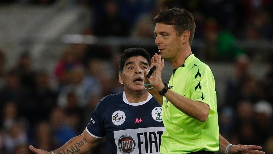 Argentine soccer legend Diego Armando Maradona argues with referee Gianluca Rocchi during an inter-religious soccer match for peace, supported by Pope Francis to promote the dialogue and peace among different religions, at Rome's Olympic Stadium, Monday, Sept. 1, 2014. (AP Photo/Gregorio Borgia)