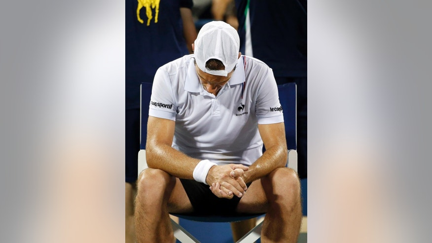 Richard Gasquet, of France, bows his head in a break between games against Gael Monfils, of France, during the third round of the U.S. Open tennis tournament Sunday, Aug. 31, 2014, in New York. (AP Photo/Jason DeCrow)