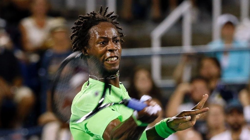 Gael Monfils, of France, returns a shot to Richard Gasquet, of France, during the third round of the U.S. Open tennis tournament Sunday, Aug. 31, 2014, in New York. (AP Photo/Jason DeCrow)