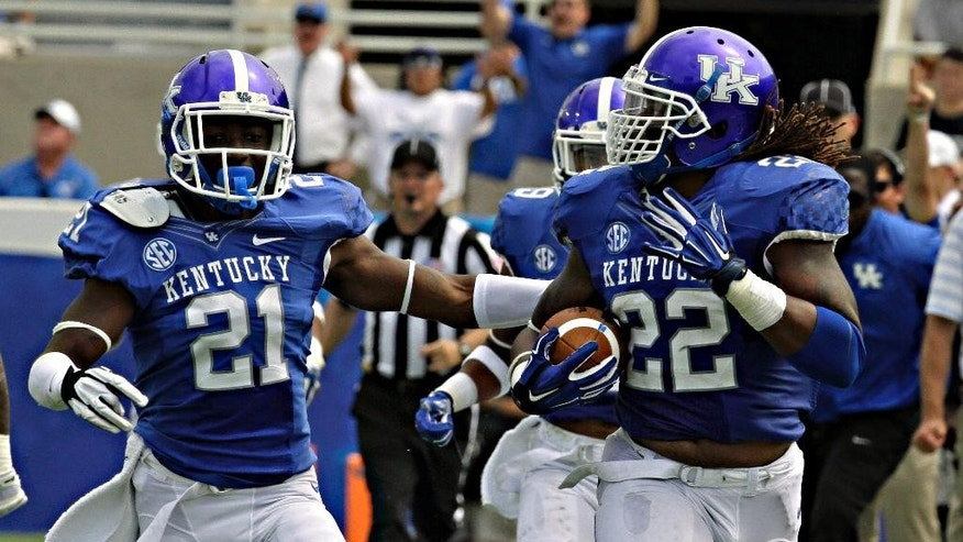 Kentucky linebacker Khalid Henderson (22) checks over his shoulder after picking up a fumble and running 89 yards for a touchdown against Tennessee-Martin in an NCAA college football game in Lexington, Ky., Saturday, Aug. 30, 2014. At left is teammate Nate Willis (21). Kentucky beat Tennessee-Martin 59-14. (AP Photo/Garry Jones)