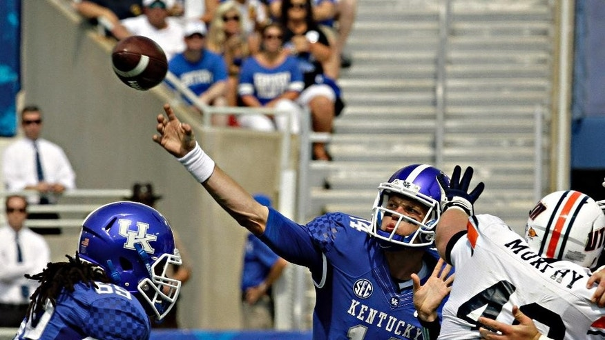Kentucky quarterback Patrick Towles (14) passes under pressure from Tennessee-Martin defensive lineman Matt Murphy (48), right,  in the first half of an NCAA college football game in Lexington, Ky., Saturday, Aug. 30, 2014. At left is Kentucky lineman Ramsey Meyers (69). (AP Photo/Garry Jones)