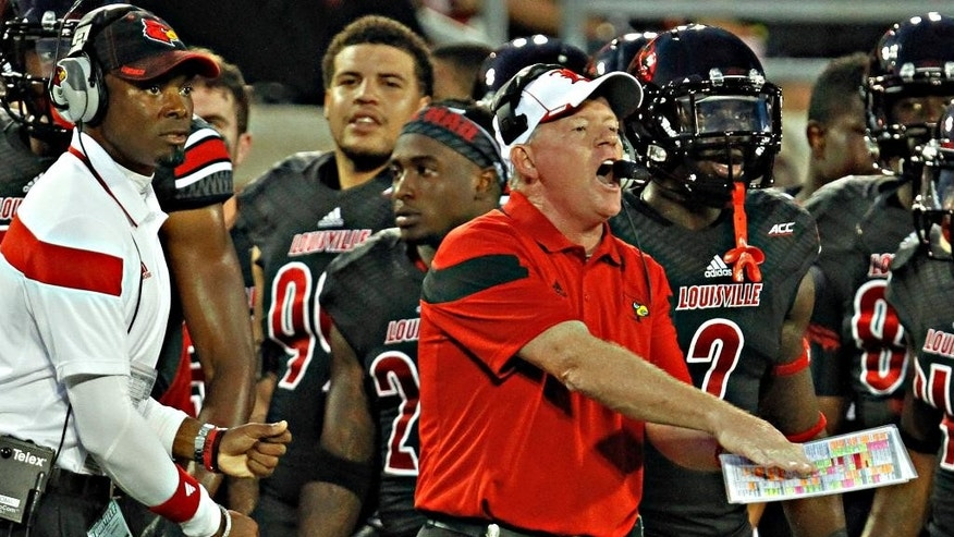Louisville coach Bobby Petrino shouts instructions to his team during the first half of a NCAA college football game against Miami in Louisville, Ky., Monday, Sept. 1, 2014. At left is wide receivers' coach Lamar Thomas. (AP Photo/Garry Jones)