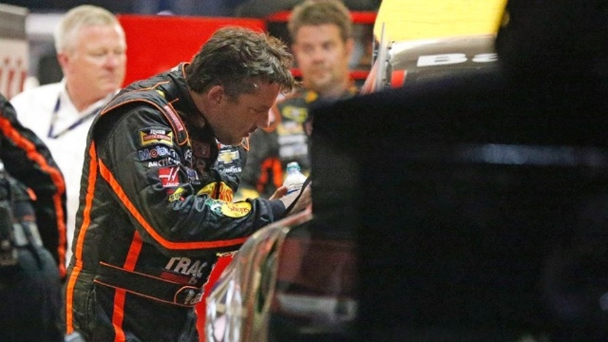 August 31, 2014: Sprint Cup Series driver Tony Stewart (14) looks over the damage to his car after he hit the wall during a NASCAR Sprint Cup auto race at Atlanta Motor Speedway in Hampton, Ga..  (AP Photo/Brynn Anderson)