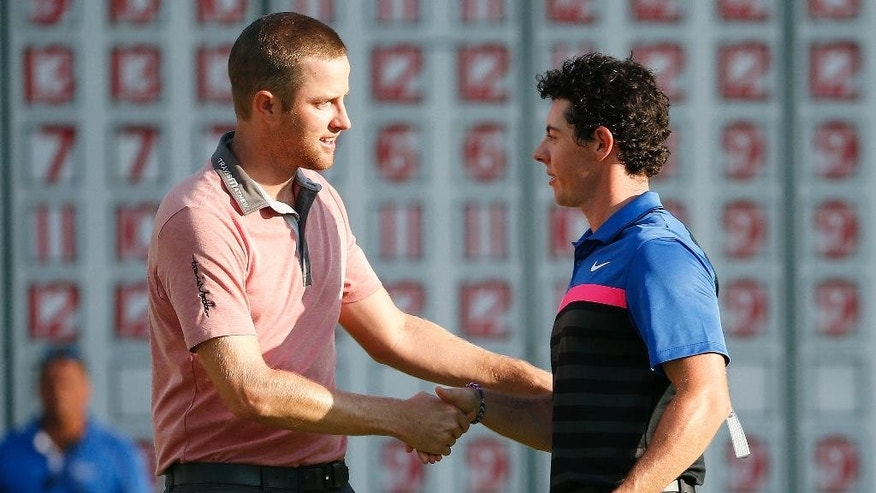 Chris Kirk, left, shakes hands with Rory McIlroy after finishing on the 18th hole of the  Deutsche Bank Championship golf tournament in Norton, Mass., Monday, Sept. 1, 2014. Kirk won with 15-under par. (AP Photo/Michael Dwyer)