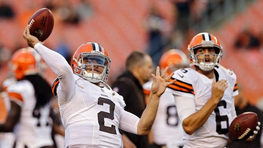 Cleveland Browns quarterback Johnny Manziel (2) warms up as Brian Hoyer (6) watches before a preseason NFL football game against the Chicago Bears, Thursday, Aug. 28, 2014, in Cleveland. (AP Photo/Tony Dejak)