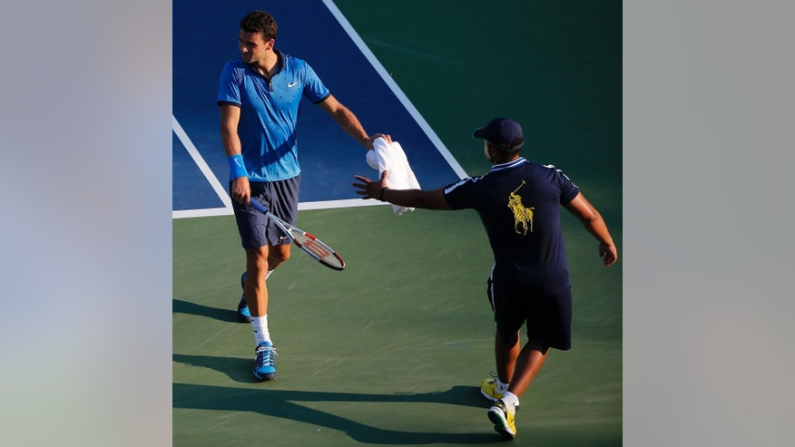 Grigor Dimitrov, of Bulgaria, hands a towel back to a ball person after wiping sweat from his face during the second round of the 2014 U.S. Open tennis tournament, Wednesday, Aug. 27, 2014, in New York. (AP Photo/Elise Amendola)