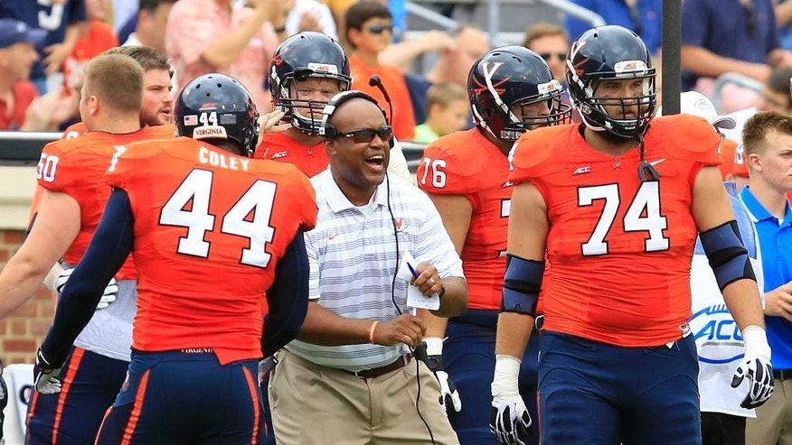 Virginia head coach Mike London, center, reacts to a play with linebacker Henry Coley (44) and guard Conner Davis (74) during the first half of an NCAA college football game against UCLA at Scott Stadium, Saturday, Aug. 30, 2014, in Charlottesville, Va. (AP Photo/Andrew Shurtleff)