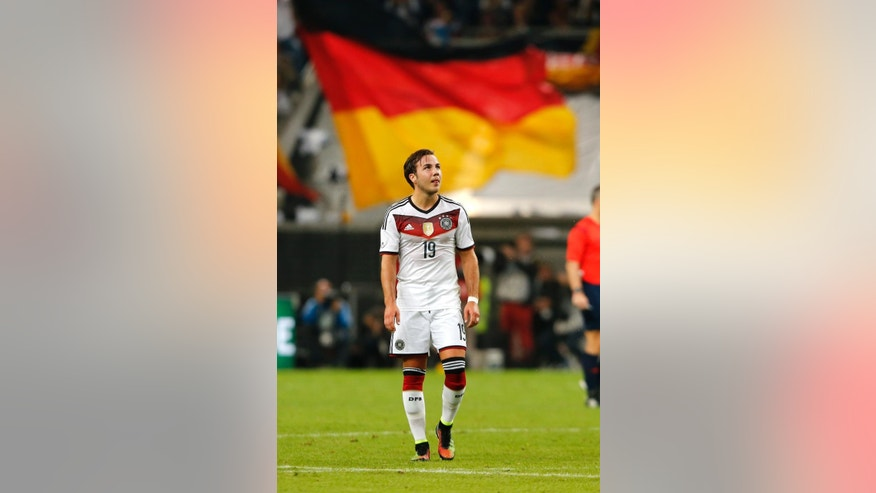 Germany's Mario Goetze walks in front of a German flag during the friendly soccer match between Germany and Argentina in Duesseldorf, Germany, Wednesday, Sept. 3, 2014. (AP Photo/Frank Augstein)