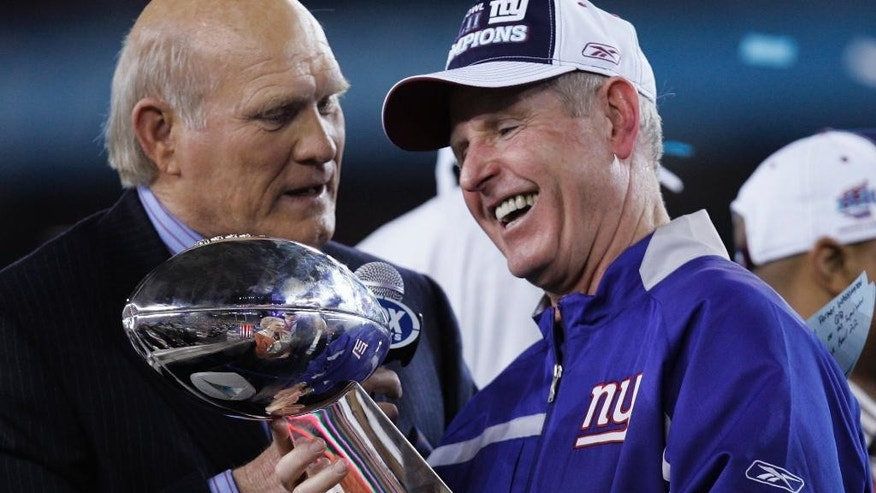 FILE - In this Feb. 3, 2008, file photo, New York Giants head coach Tom Coughlin, right, admires the Vince Lombardi Trophy with broadcaster Terry Bradshaw after the Giants beat the New England Patriots 17-14 in the Super Bowl XLII football game in Glendale, Ariz. The Giants have missed the playoffs the past two years, don't assume 68-year-old Coughlin is on the hot seat entering the season. Winning two Super Bowls far outweighs two poor season. (AP Photo/David Duprey, File)