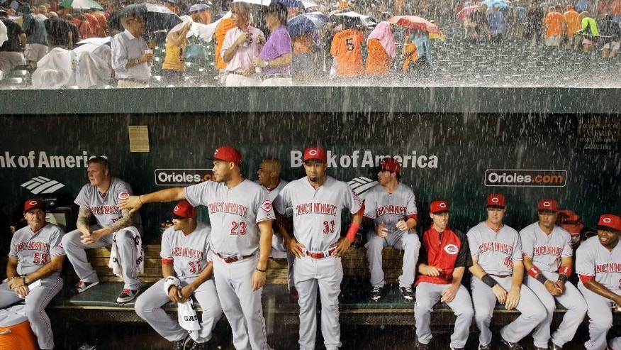 Members of the Cincinnati Reds watch from the dugout as heavy rain falls during a rain delay in the first inning of an interleague baseball game against the Baltimore Orioles, Tuesday, Sept. 2, 2014, in Baltimore. (AP Photo/Patrick Semansky)