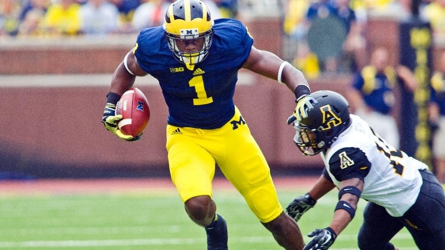 Michigan wide receiver Devin Funchess (1) breaks away from Appalachian State defensive back A.J. Howard, bottom, in the first quarter of  an NCAA college football game in Ann Arbor, Mich., Saturday, Aug. 30, 2014. (AP Photo/Tony Ding)