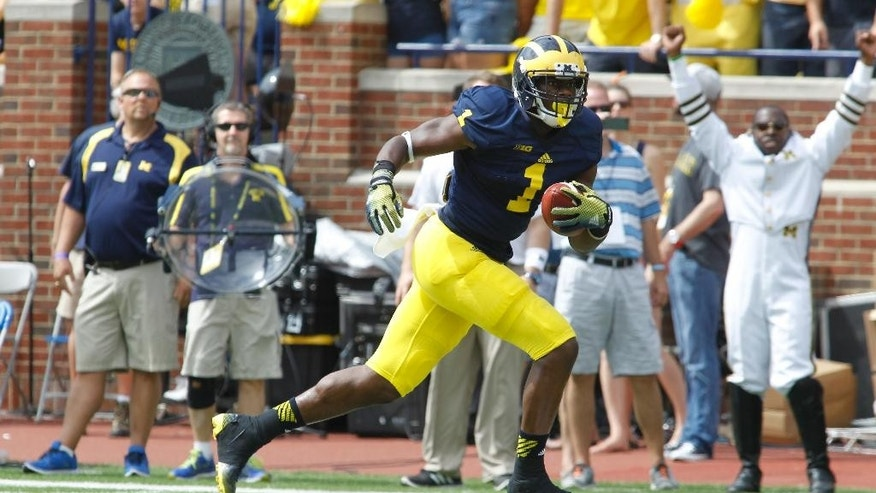 Michigan wide receiver Devin Funchess (1)  rushes for a touchdown after making a catch in the first quarter of an NCAA college football game against Appalachian State in Ann Arbor, Mich., Saturday, Aug 30, 2014. (AP Photo/Tony Ding)